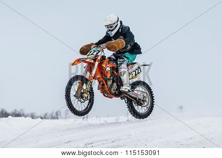 racer motorcycle rides at speed on a snowy motocross track