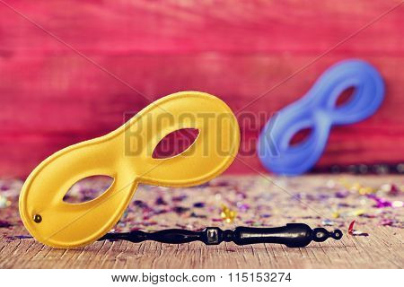 two handled carnival masks, one yellow and one blue, and confetti of different colors on a rustic wooden surface, against a rustic red background