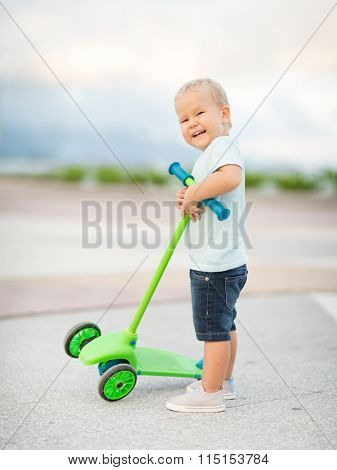 Boy with scooter outdoor. Leisure activity