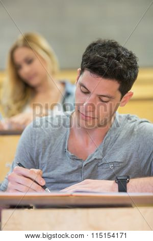 Serious male student during class in the lecture hall