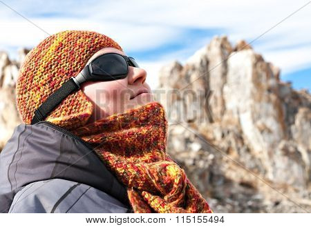 Portrait of a girl in orange scarves and hats against the blue sky and snow-capped mountains. The mountain sports glasses looking up. Bright sunny winter day.  Olkhon Island on Lake Baikal