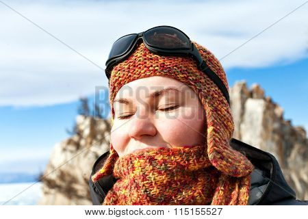 Portrait of a girl in orange scarves and hats against the blue sky and snowy mountains. Closed eyes. Sport mountain sunglasses. Bright sunny winter day. Shaman on Lake Baikal. Olkhon Island.