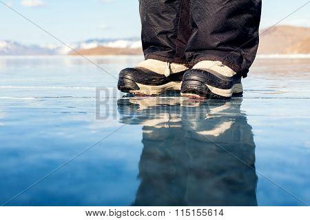 Reflection. Legs of man on ice.