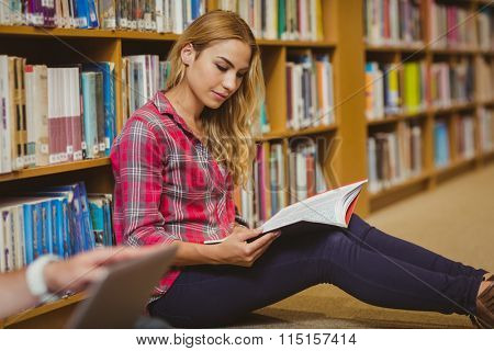 Concentrated female student working on floor in library