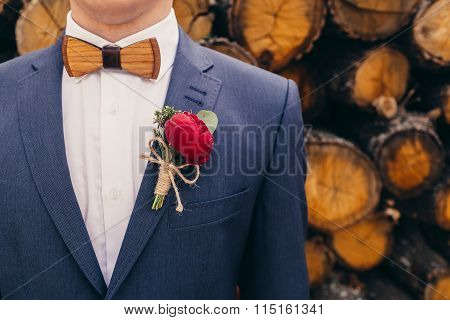 Grooms With Wooden Bow-tie And Red Rose Boutonniere On Wooden Background