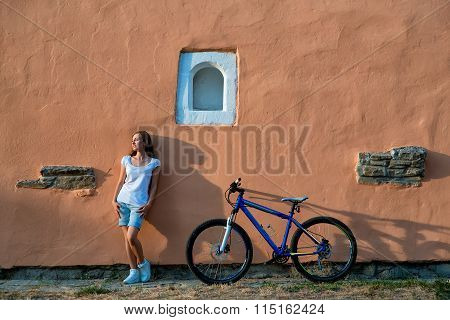 Young woman sensual posing with bicycle in city