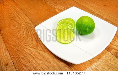 Juicy Slices Of Lime On A White Saucer