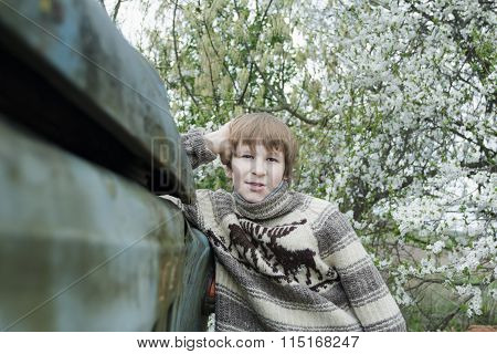 Teenage Boy With Knitted Woolly Reindeer Warm Sweater Leaning Old Truck Body Outdoors Near Blooming