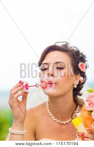beautiful bride blowing bubbles