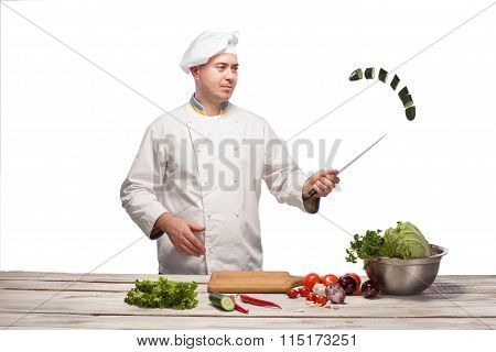 Chef cutting a green cucumber in his kitchen