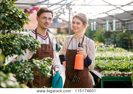 Happy man and woman gardeners holding watering can and pulveriser for spraying flowers and plants in greenhouse