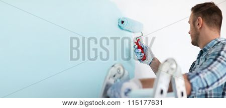 close up of male in gloves holding painting roller