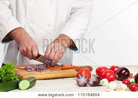 Chef cutting a onion on his kitchen