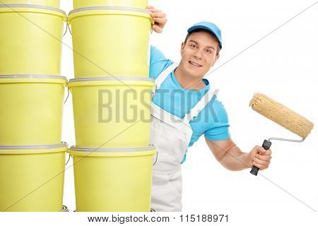 Young male decorator holding a paint roller and posing behind a stack of color buckets isolated on white background