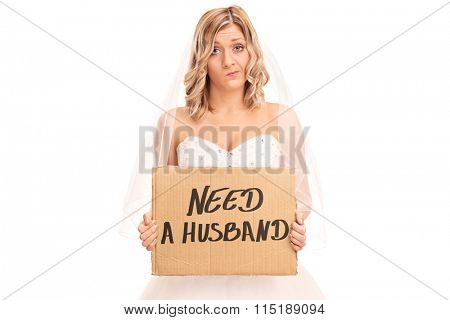 Young blond bride holding a banner that says need a husband isolated on white background