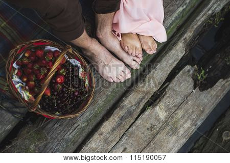 Man And Woman Feet On Wooden Bridge Near The Basket With Berries