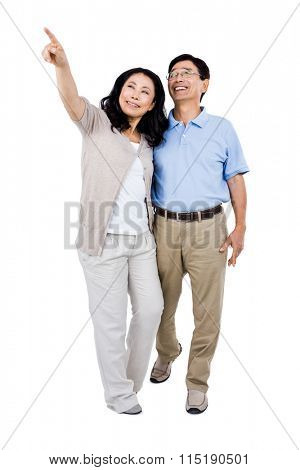 Smiling couple holding each other and pointing upwards