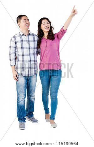 Happy couple pointing upwards against white background
