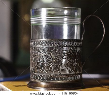 Old used nickel silver glass holder with dark background.