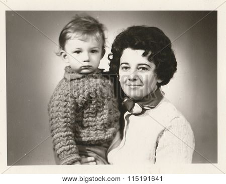 Retro photo of mother and her son. Portrait photo was taken in photo studio photo with dark tint