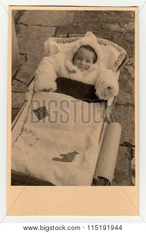 Vintage photos shows baby girl in a pram (baby carriage) circa 1940.