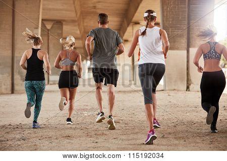 Group Of Runners Running Under A Bridge
