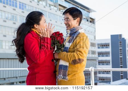 Older asian couple on balcony with roses on a cold day