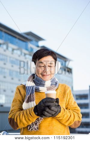 Older asian man with coffee to go on a cold day