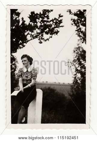 Vintage photo shows a young girl leans against verge post circa 1930.