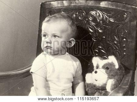 Retro photo of a small boy with teddy bear. Portrait photo was taken in photo studio circa 1972.