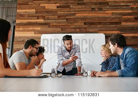 Young Man With Colleagues Discussing New Project