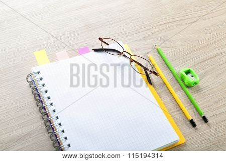 Opened notebook with stationery on grey wooden background