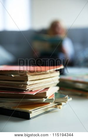 Pile of old books on white table. Focus on books and blurred background