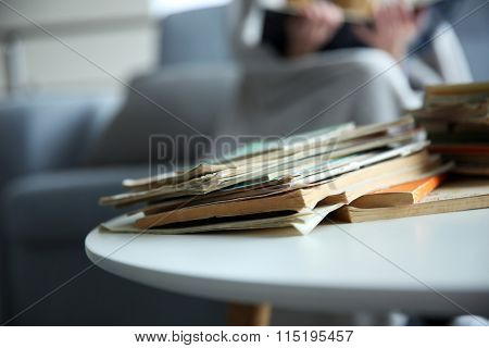 Pile of old books on white table in the room. Focus on books and blurred background