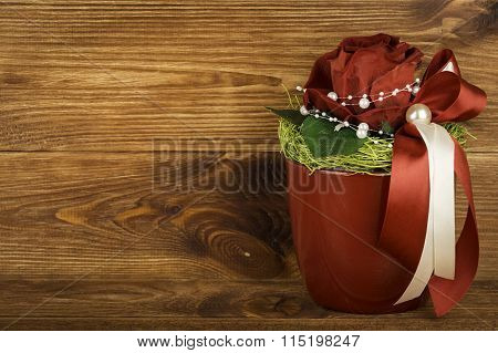 Florist composition with red rose on wooden background.