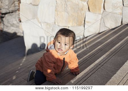 Cute Chinese Baby Boy Crawling On Stairs Outdoors