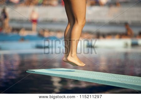 Jump. Lady diver preparing to dive from the springboard.