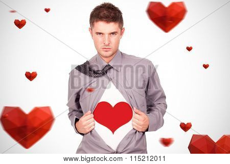young attractive man pulling at his tshirt against red heart