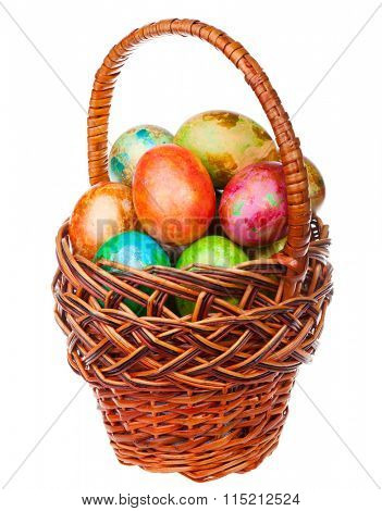 Colored easter eggs in a wicker basket isolated on white background