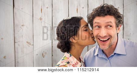 Pretty woman kissing man on cheek against wooden background