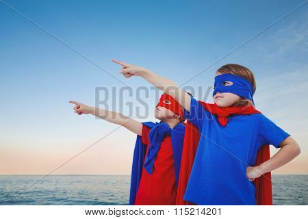 Masked kids pretending to be superheroes against beautiful sunset on a sunny day