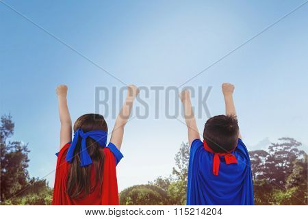 Masked kids pretending to be superheroes against park on sunny day