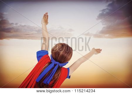 Masked girl pretending to be superhero against beautiful orange and blue sky