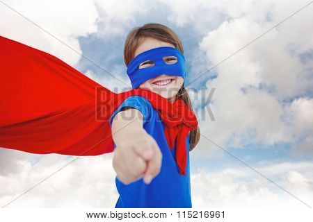 Smiling masked girl pretending to be superhero against blue sky with white clouds