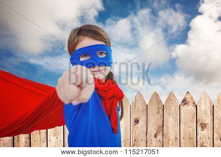Masked girl pretending to be superhero against fence under blue sky