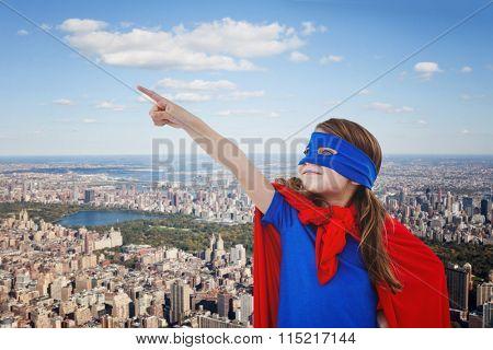 Masked girl pretending to be superhero against new york