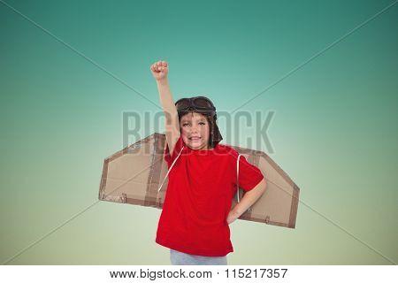 Boy pretending to be a pilot against blue sky