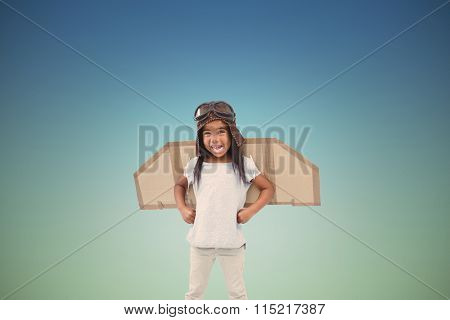 Standing girl with fake wings pretending to be pilot against blue sky
