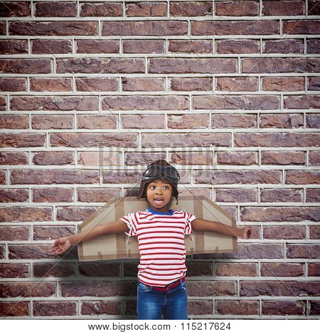 Smiling boy pretending to be pilot against red brick wall