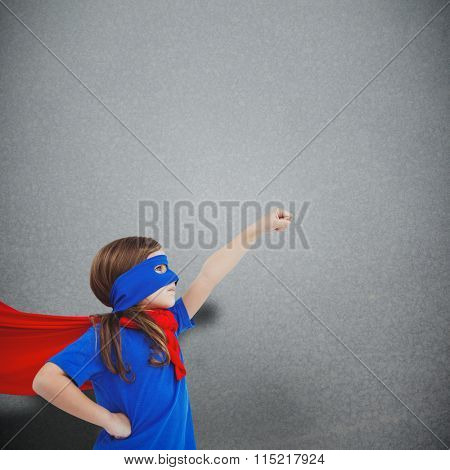 Masked girl pretending to be superhero against grey background